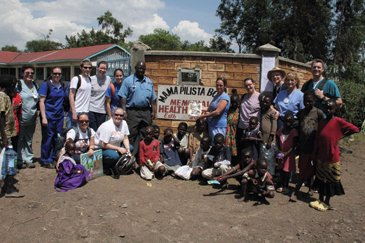 A group of us standing at the gate of the Mama Palista clinic. I'm holding a copy of akronlife.