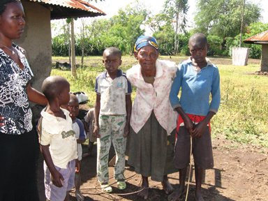 The author's sponsored child, Roy Omandi, and his family - his grandmother and five boys. His aunt stands nearby with a cousin. Their mud hut is on the left.
