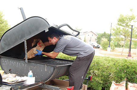 Photo-5---Nosh-Eatery's-Brian-Teggart-replenishes-the-charcoal-in-his-grill.jpg